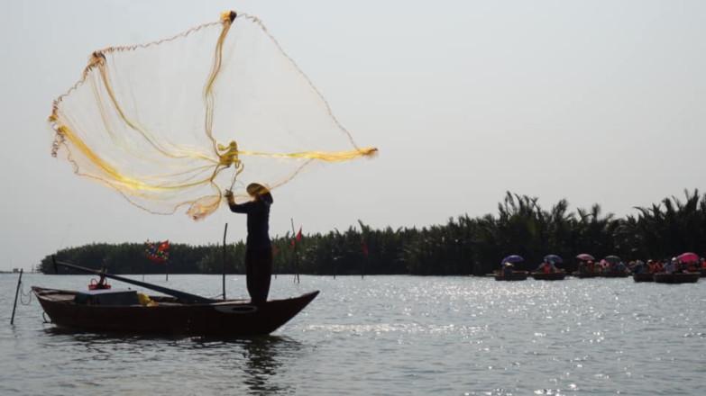 그 남자는 베트남의 전통 낚시를 보여준다